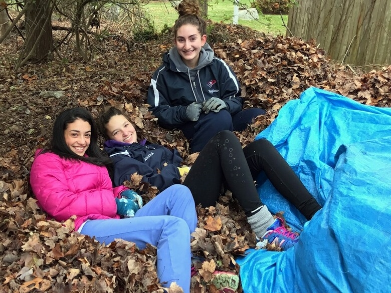 Kayla Cohen, Elena Ariola and Hannah Rigoglioso relax with tarp after hauling leaves
